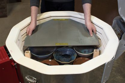 Advancer kiln shelf being lowered into a top loading Skutt electric kiln.