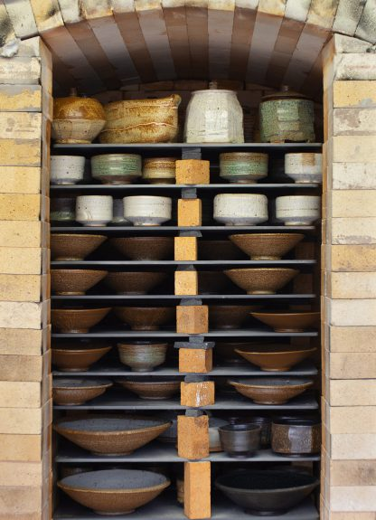Advancer kiln shelves stacked with pots on them in a gas reduction kiln.